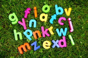 Children's alphabet blocks arranged on grass.